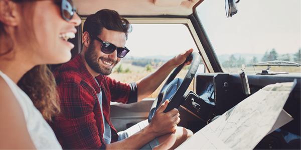 Un homme au volant d'une voiture sourit en regardant une femme qui rit sur le siège passager, tenant une feuille de route en papier.